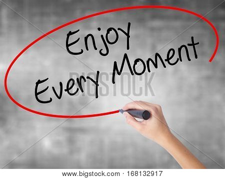 Woman Hand Writing Enjoy Every Moment With Black Marker Over Transparent Board.