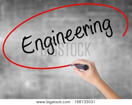 Woman Hand Writing Engineering  With Black Marker Over Transparent Board