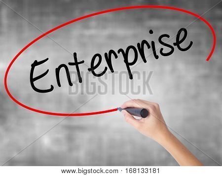 Woman Hand Writing Enterprise With Black Marker Over Transparent Board