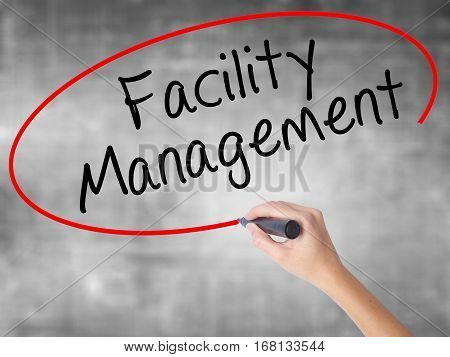 Woman Hand Writing Facility Management With Black Marker Over Transparent Board