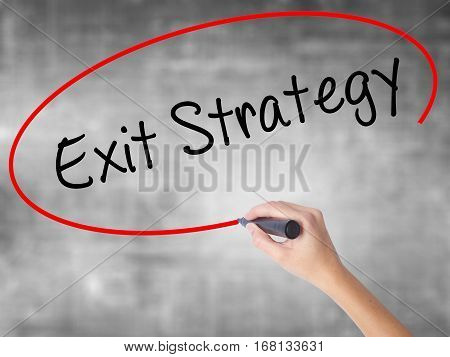 Woman Hand Writing Exit Strategy With Black Marker Over Transparent Board.