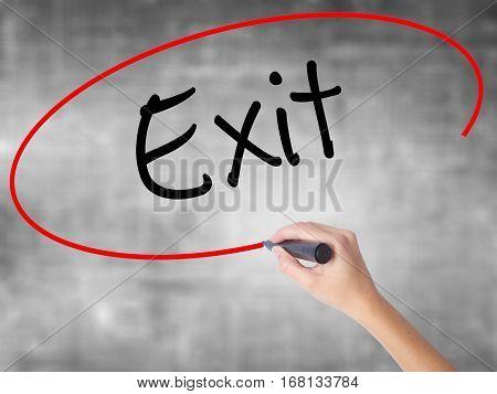 Woman Hand Writing Exit With Black Marker Over Transparent Board