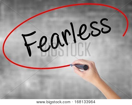 Woman Hand Writing Fearless With Black Marker Over Transparent Board.
