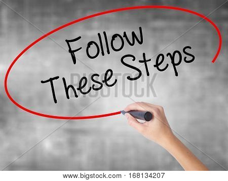 Woman Hand Writing Follow These Steps With Black Marker Over Transparent Board