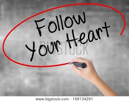 Woman Hand Writing Follow Your Heart With Black Marker Over Transparent Board