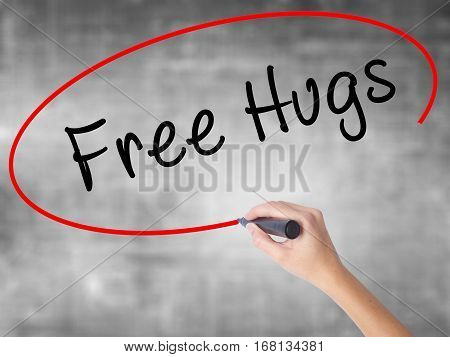 Woman Hand Writing Free Hugs With Black Marker Over Transparent Board