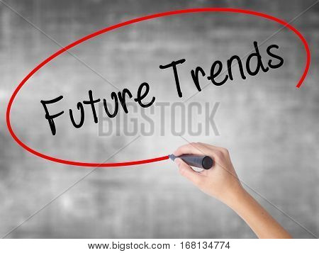 Woman Hand Writing Future Trends With Black Marker Over Transparent Board