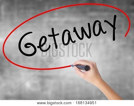 Woman Hand Writing Getaway With Black Marker Over Transparent Board