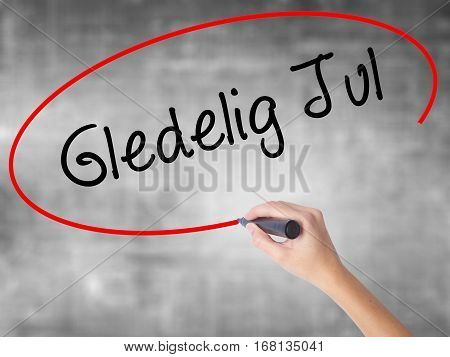 Woman Hand Writing Gledelig Jul  (happy Christmas In Norwegian) With Black Marker Over Transparent B