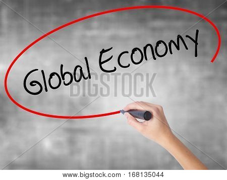 Woman Hand Writing Global Economy With Black Marker Over Transparent Board