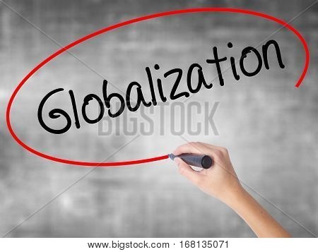 Woman Hand Writing Globalization With Black Marker Over Transparent Board.