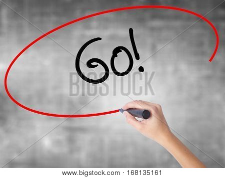 Woman Hand Writing Go! With Black Marker Over Transparent Board