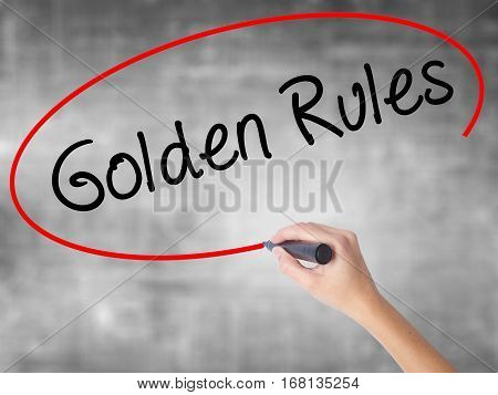 Woman Hand Writing Golden Rules With Black Marker Over Transparent Board