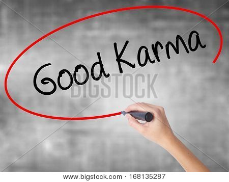Woman Hand Writing  Good Karma With Black Marker Over Transparent Board