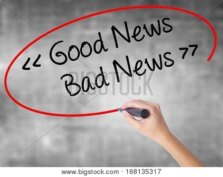 Woman Hand Writing Good News - Bad News With Black Marker Over Transparent Board.