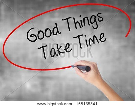 Woman Hand Writing Good Things Take Time With Black Marker Over Transparent Board