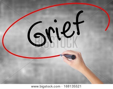Woman Hand Writing Grief With Black Marker Over Transparent Board
