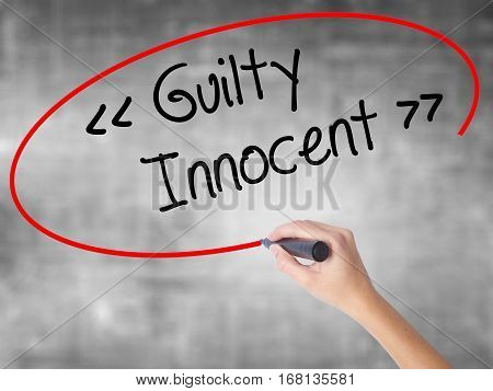 Woman Hand Writing Guilty - Innocent With Black Marker Over Transparent Board.