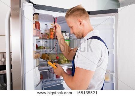 Young Repairman Checking Refrigerator With Digital Multimeter