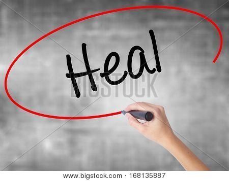 Woman Hand Writing  Heal  With Black Marker Over Transparent Board