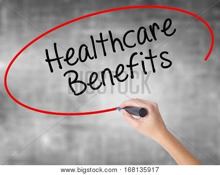 Woman Hand Writing Healthcare Benefits With Black Marker Over Transparent Board