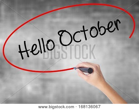 Woman Hand Writing  Hello October  With Black Marker Over Transparent Board