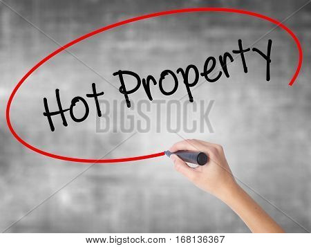 Woman Hand Writing Hot Property With Black Marker Over Transparent Board