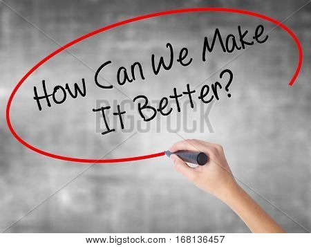 Woman Hand Writing How Can We Make It Better? With Black Marker Over Transparent Board
