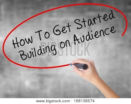 Woman Hand Writing How To Get Started Building On Audience With Black Marker Over Transparent Board