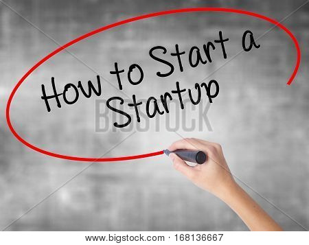 Woman Hand Writing How To Start A Startup With Black Marker Over Transparent Board