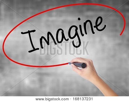 Woman Hand Writing Imagine  With Black Marker Over Transparent Board