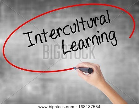 Woman Hand Writing Intercultural Learning With Black Marker Over Transparent Board