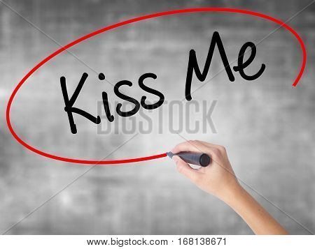 Woman Hand Writing Kiss Me With Black Marker Over Transparent Board