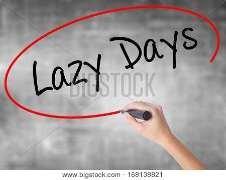 Woman Hand Writing Lazy Days With Black Marker Over Transparent Board.