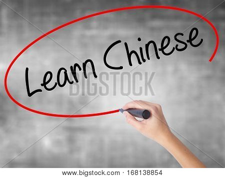 Woman Hand Writing Learn Chinese With Black Marker Over Transparent Board.