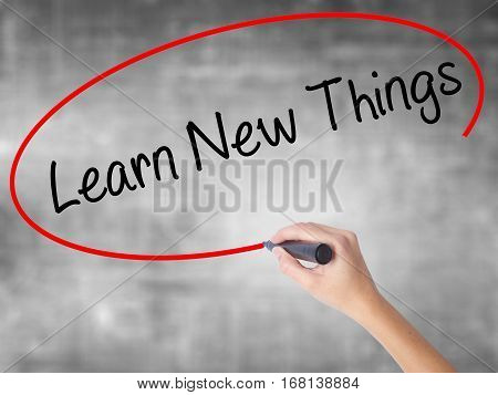 Woman Hand Writing Learn New Things With Black Marker Over Transparent Board