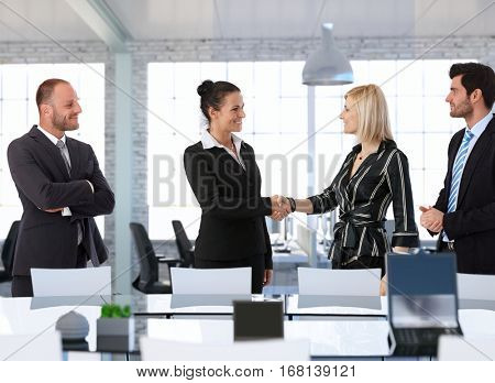 Happy businesswomen shaking hands in office before business meeting.