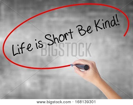Woman Hand Writing Life Is Short Be Kind! With Black Marker Over Transparent Board