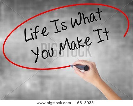 Woman Hand Writing Life Is What You Make It With Black Marker Over Transparent Board