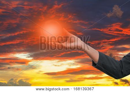 business man receiving hand holding the light in palm of idea on sky red background