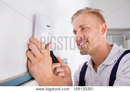 Male Electrician Installing Security System Door Sensor On Wall
