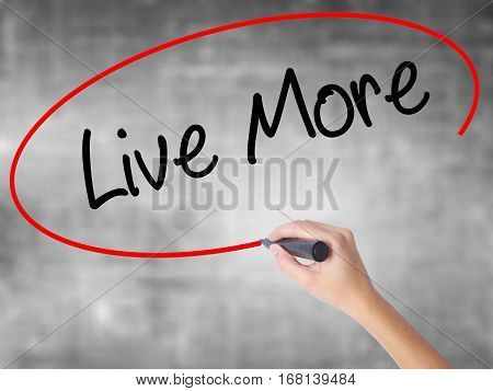 Woman Hand Writing Live More With Black Marker Over Transparent Board