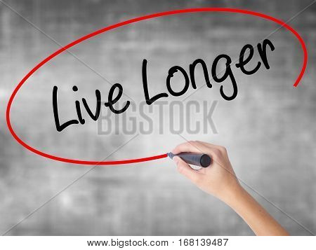Woman Hand Writing Live Longer With Black Marker Over Transparent Board