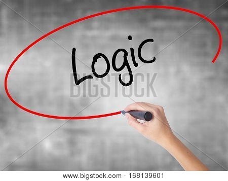 Woman Hand Writing Logic With Black Marker Over Transparent Board