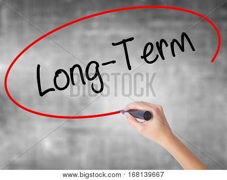 Woman Hand Writing Long-term With Black Marker Over Transparent Board