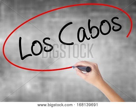 Woman Hand Writing Los Cabos With Black Marker Over Transparent Board