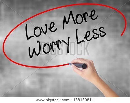 Woman Hand Writing Love More Worry Less With Black Marker Over Transparent Board.