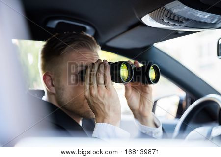 Man Sitting In Car Doing Surveillance Looking Through Binocular