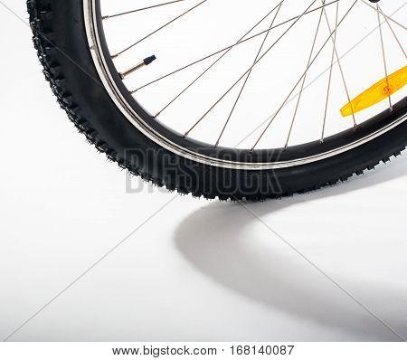 Bicycle wheel with orange reflector, shallow DOF.