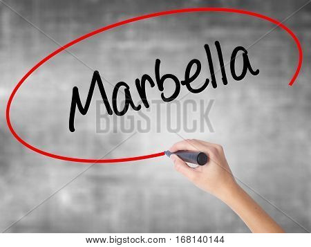 Woman Hand Writing Marbella With Black Marker Over Transparent Board